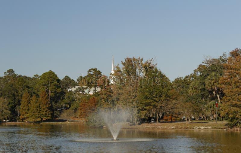 Vista del lago della fontana degli alberi e della chiesa Steeple immagine stock