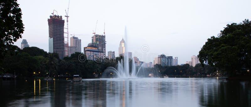 Vista del lago park de Lumphini con los edificios en Bangkok con la luz de la puesta del sol foto de archivo libre de regalías