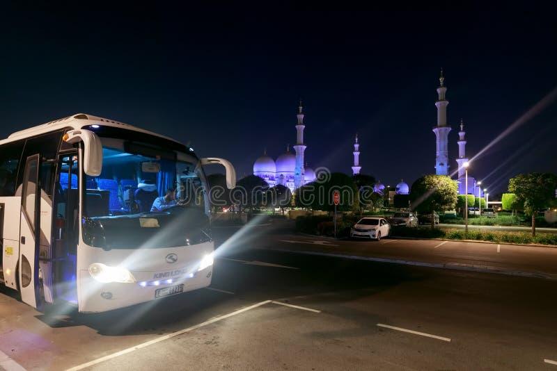 Vista del magnífico Sheikh Zayed Grand Mosque con las luces azules hermosas por la tarde y los turistas que esperan i del autobús imagen de archivo libre de regalías