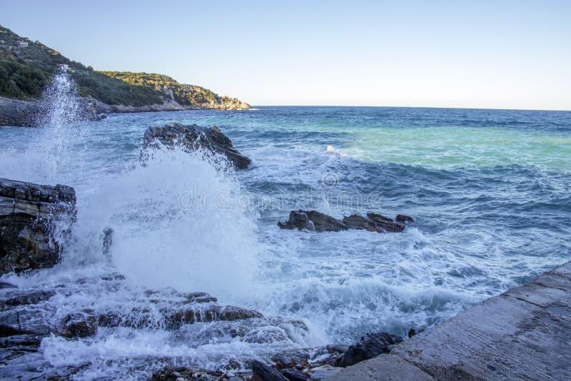 Vista del mar y de las colinas del embarcadero Salpica del agua de las ondas del mar que se estrellan contra los acantilados de p fotografía de archivo