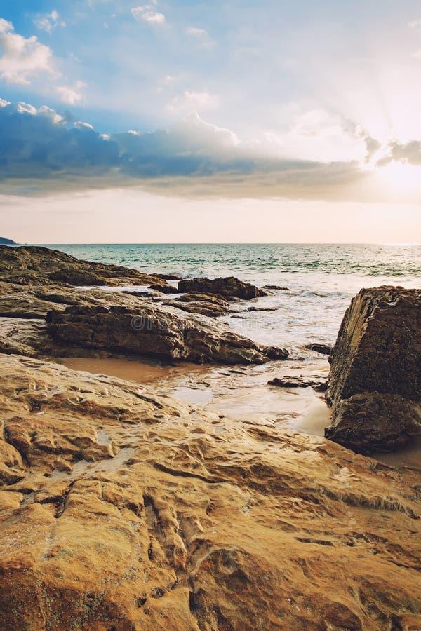 Vista del mar y piedras y playa azules en la puesta del sol foto de archivo
