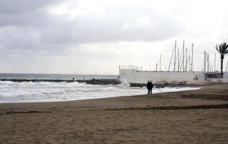 Vista del mare di inverno Sabbia bagnata, spiaggia vuota, mare freddo, nuvole di pioggia grige Depressione di tristezza immagine stock libera da diritti