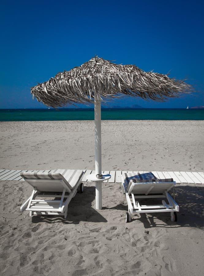 Vista del mare e della spiaggia con il parasole e due letti e cieli blu fotografie stock