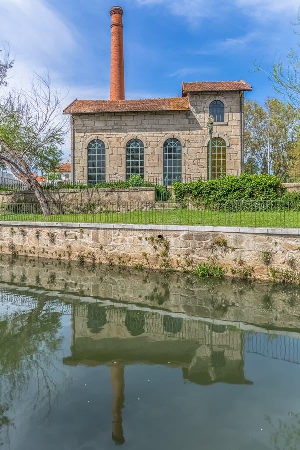 Vista del museo de la electricidad, edificio con la chimenea en el ladrillo industrial, duplicado en el río de Paiva fotos de archivo