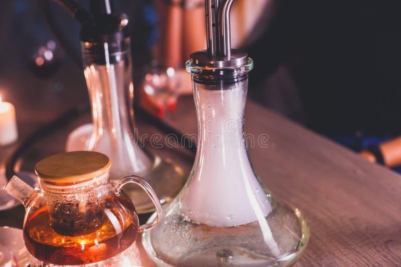 Vista del narghilé con le candele e del fumo su una tavola, salotto del narghilé con i giovani che fumano nei precedenti, club de fotografie stock