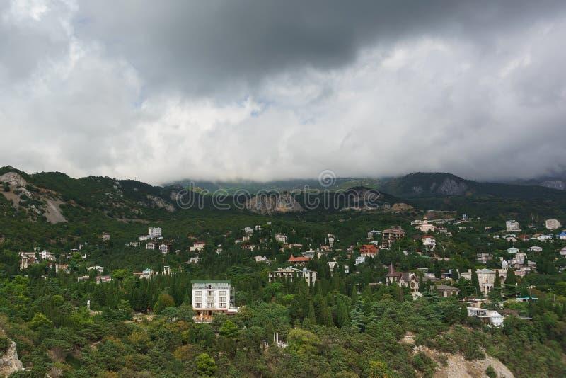 Vista del paesaggio dalla diva della roccia sul villaggio Simeiz della località di soggiorno Sopra le cime delle montagne che app fotografie stock libere da diritti