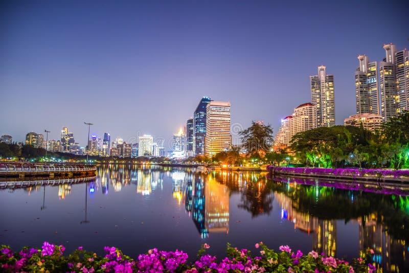 Vista del paisaje urbano de la noche en el parque de Benchakitti, edificio moderno de Bangkok, Tailandia, fotos de la reflexión,  foto de archivo
