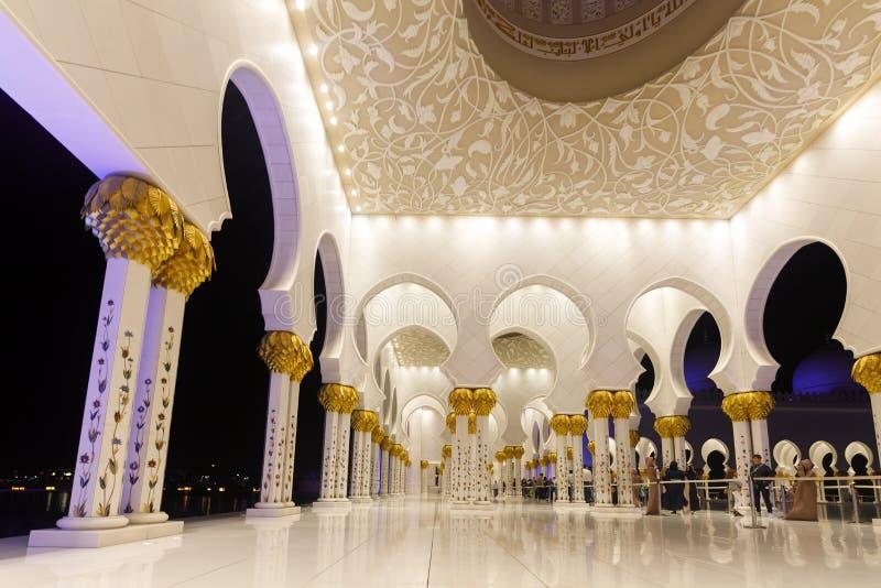 Vista del passaggio con gli arché di Sheikh Zayed Grand Mosque con le colonne di marmo decorate con le immagini dei mosaici e del fotografie stock libere da diritti