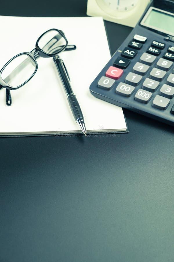 Vista del piano d'appoggio della penna, del taccuino e del calcolatore sulla scrivania fotografia stock