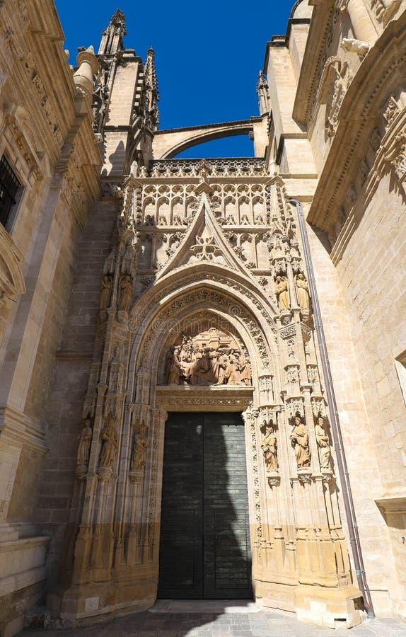 Vista del portone dell'entrata della cattedrale di Siviglia con il Giralda nei precedenti fotografia stock
