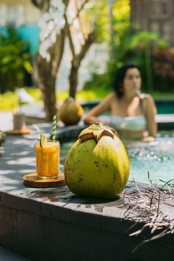 vista del primo piano dei cocktail tropicali freschi su priorità alta e sulla ragazza che riposano nello stagno dietro fotografia stock libera da diritti