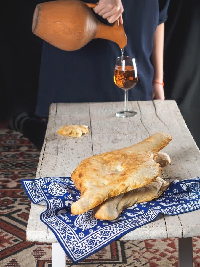Vista del primo piano dei flatbreads georgiani tradizionali e del vino domestico di versamento della persona dalla brocca dell'ar fotografia stock libera da diritti