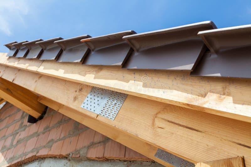 Vista del primo piano del dettaglio del tetto con le travi e le mattonelle di tetto di legno Nuova casa in costruzione fotografie stock