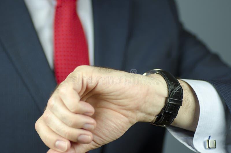 Vista del primo piano del responsabile in vestito e del legame che esamina orologio fotografia stock