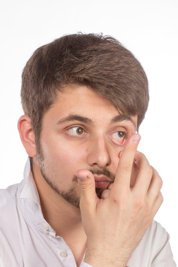 Vista del primo piano dell'occhio marrone di un uomo mentre inserendo una c correttiva fotografia stock libera da diritti