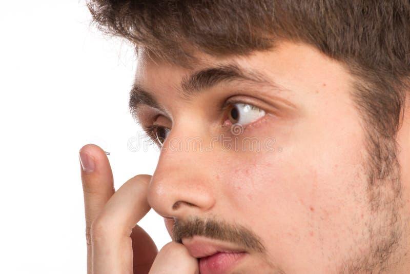 Vista del primo piano dell'occhio marrone di un uomo mentre inserendo una c correttiva immagini stock libere da diritti