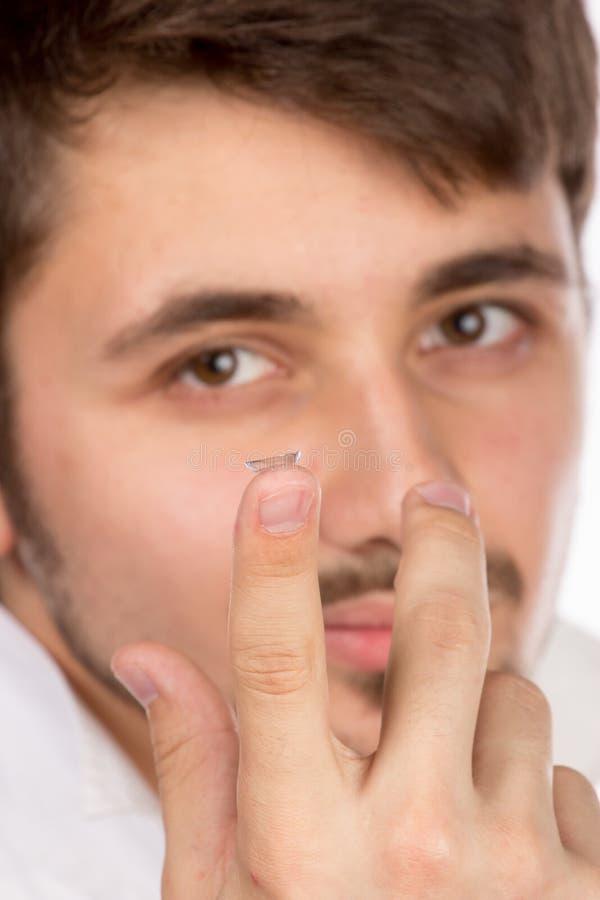 Vista del primo piano dell'occhio marrone di un uomo mentre inserendo una c correttiva fotografie stock