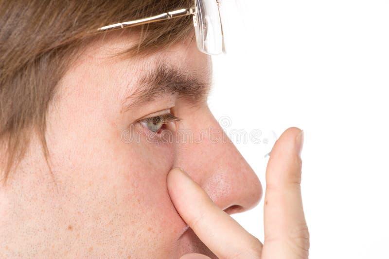 Vista del primo piano dell'occhio marrone di un uomo mentre inserendo una c correttiva immagine stock