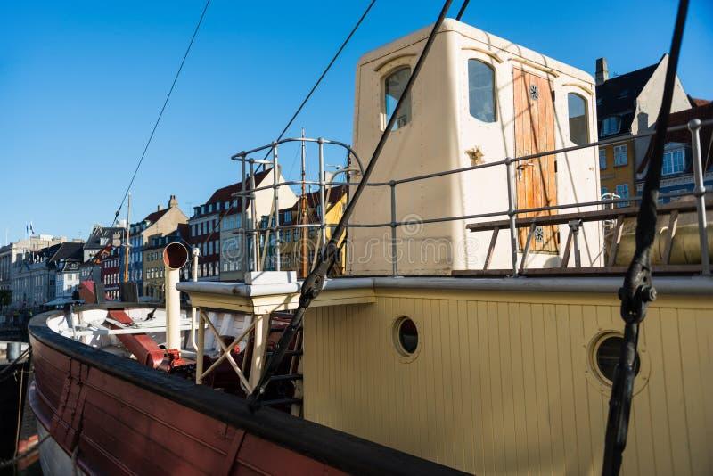 vista del primo piano della barca e delle case variopinte dietro al pilastro di Nyhavn a Copenhaghen, Danimarca immagine stock libera da diritti