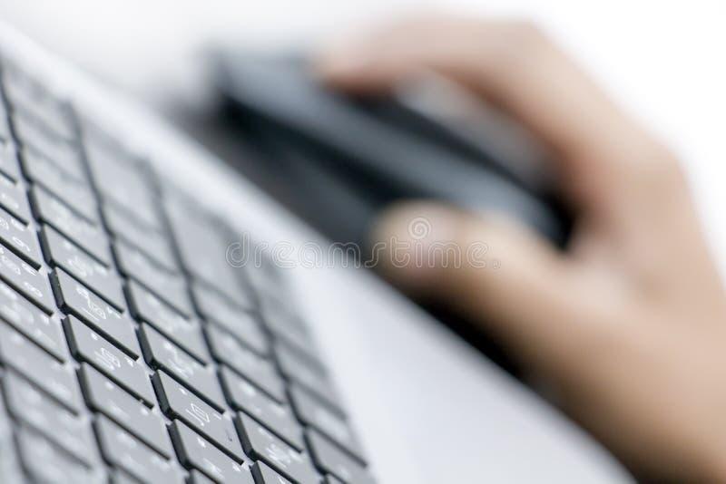 Vista del primo piano della tastiera con la mano sul topo fotografia stock