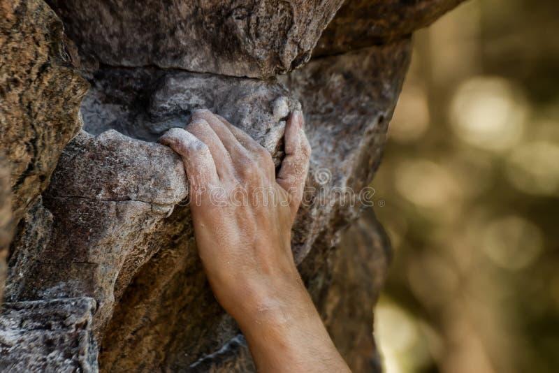 Vista del primo piano della tenuta commovente della mano del ` s dello scalatore sulla scogliera naturale immagini stock