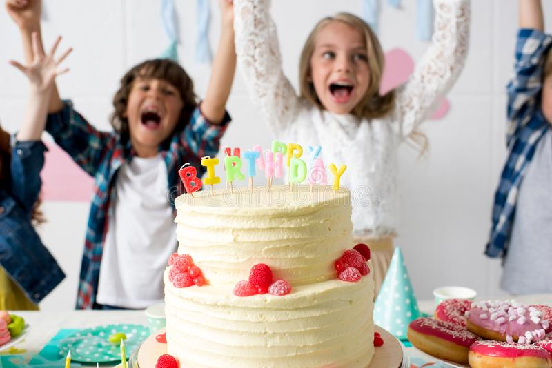 vista del primo piano della torta di compleanno deliziosa sulla tavola festiva e sull'innalzamento allegro dei bambini immagini stock