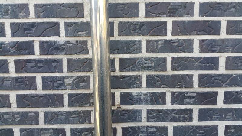 Vista del primo piano della tubatura dell'acqua d'argento sopra il muro di mattoni nero Nel sole fotografia stock
