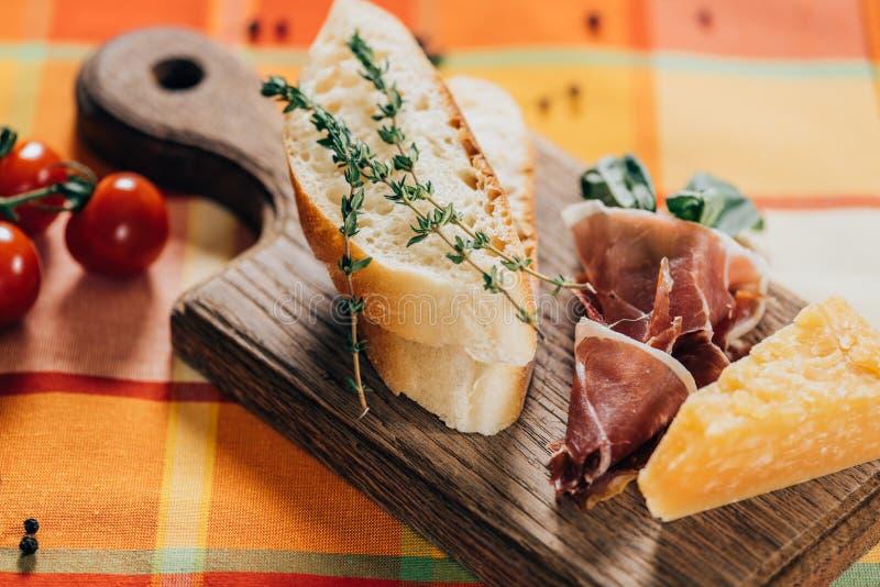 vista del primo piano delle baguette, della carne e del parmigiano affettati su di legno immagine stock