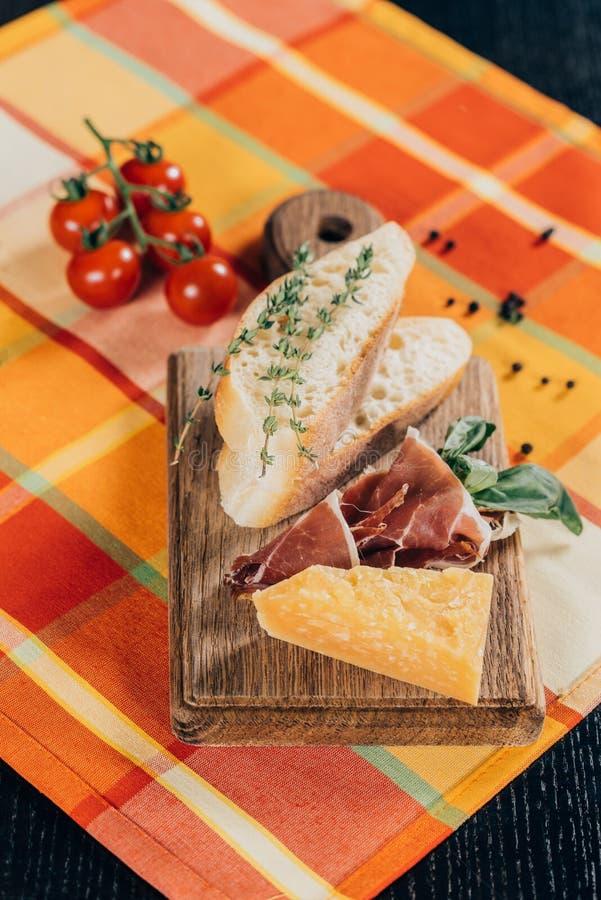 vista del primo piano delle baguette, della carne e del parmigiano affettati sul tagliere di legno e sui pomodori ciliegia fresch immagini stock