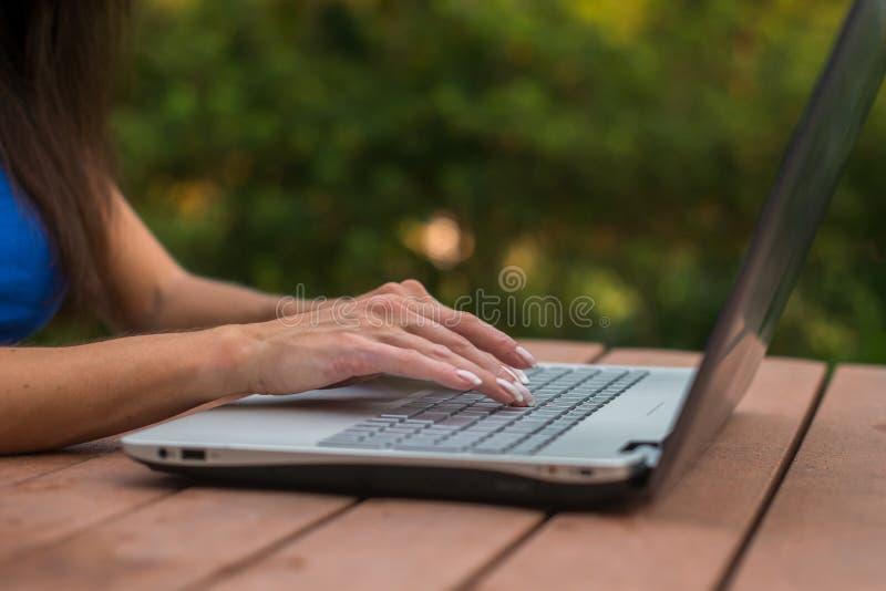 Vista del primo piano delle mani femminili sulla tastiera del computer portatile Studente che impara all'aperto immagini stock
