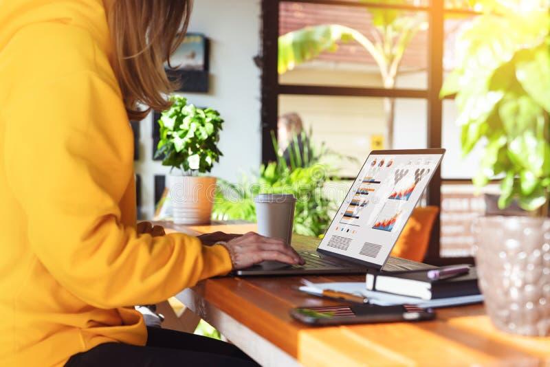 Vista del primo piano dello schermo del computer portatile con i grafici, diagrammi sul monitor Ragazza negli impianti gialli di  fotografia stock libera da diritti