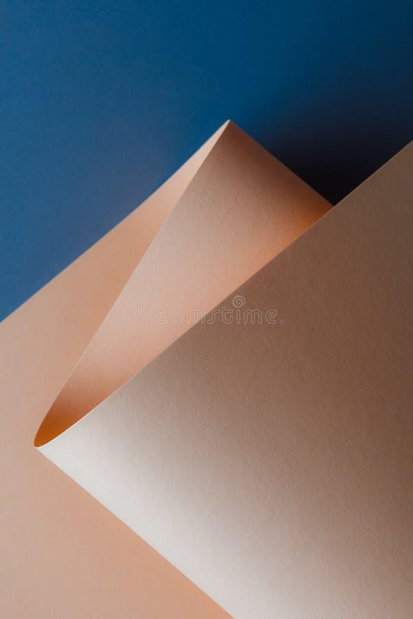 vista del primo piano di bello strato di carta beige tenero su fondo blu scuro immagine stock