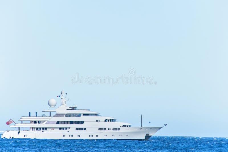 Vista del primo piano di luce del giorno agli yacht bianchi che girano sull'isolato dell'acqua immagine stock
