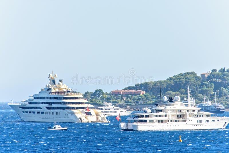 Vista del primo piano di luce del giorno agli yacht bianchi con gli elicotteri a bordo immagine stock