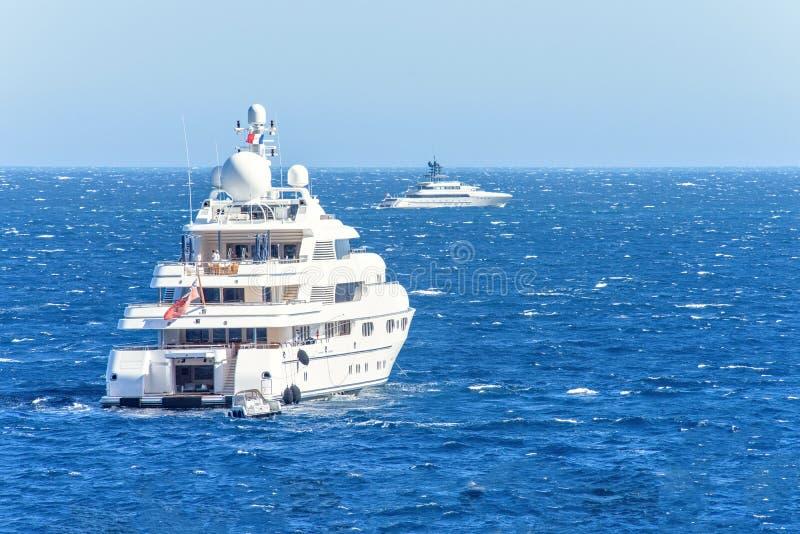 Vista del primo piano di luce del giorno agli yacht bianchi con la gente a bordo immagini stock