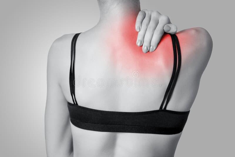 Vista del primo piano di una giovane donna con la spalla o di un dolore al collo su gray fotografia stock libera da diritti
