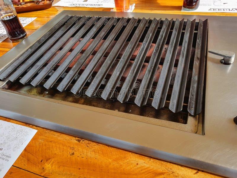 Vista del primo piano di una griglia per carne o bistecca dove la gente cucina il loro proprio alimento in un ristorante immagine stock libera da diritti
