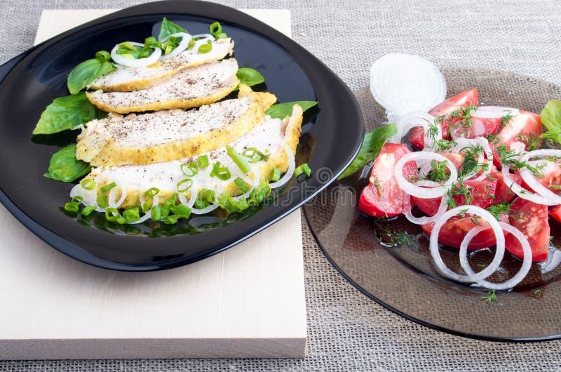 Vista del primo piano sulle fette arrostite di raccordo del pollo e di insalata del pomodoro immagine stock