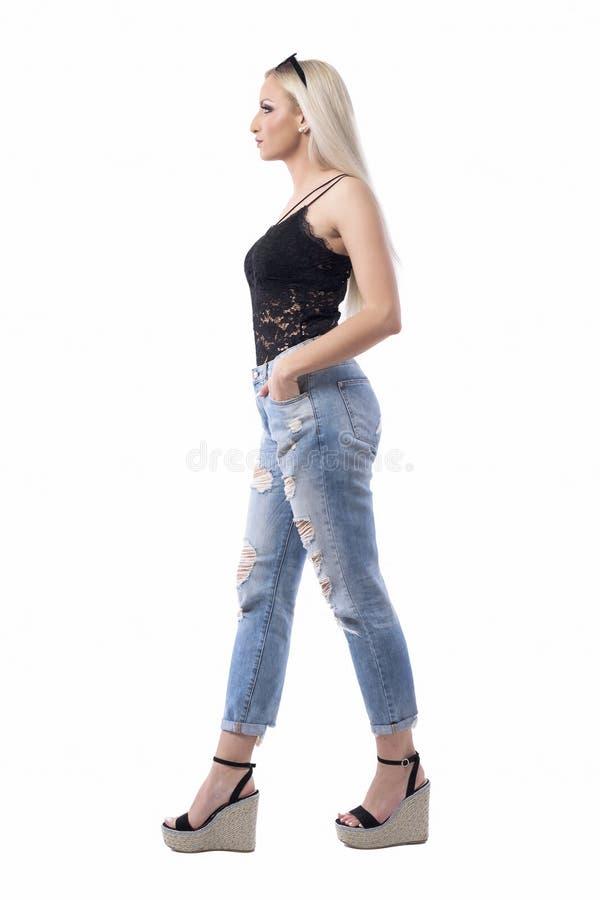 Vista del profilo di una ragazza bionda bionda, che cammina alla moda, in jeans fotografia stock libera da diritti