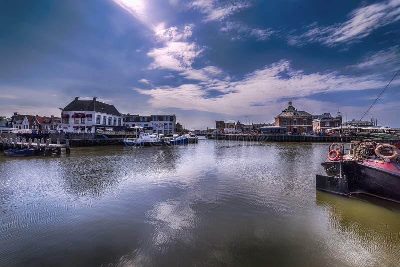 Vista del puerto de Harlingen Países Bajos, en un día soleado claro Para ver cómo el cielo claro nublado refleja en el agua sin v foto de archivo libre de regalías