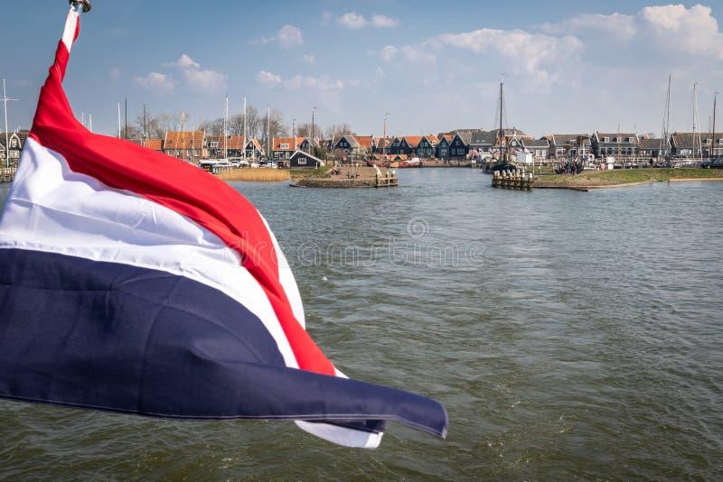 Vista del puerto de Marken del transbordador expreso de Volendam Marken Bandera holandesa en la popa del barco imagenes de archivo