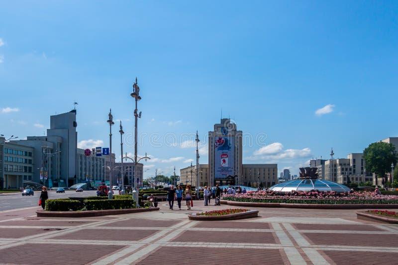 Vista del quadrato di città della gente e delle costruzioni contro cielo blu a Minsk Bielorussia immagini stock