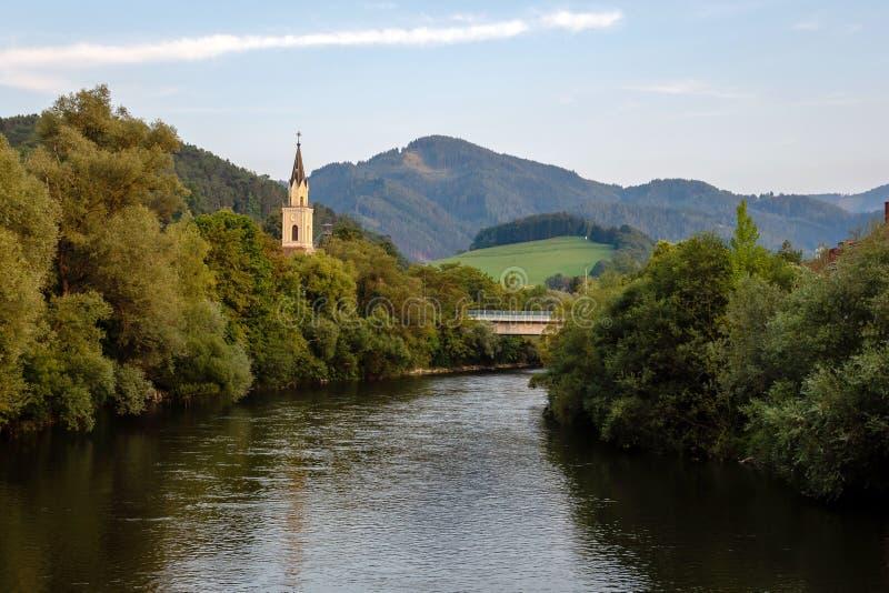 Vista del río de la MUR con la iglesia en Leoben, Austria foto de archivo