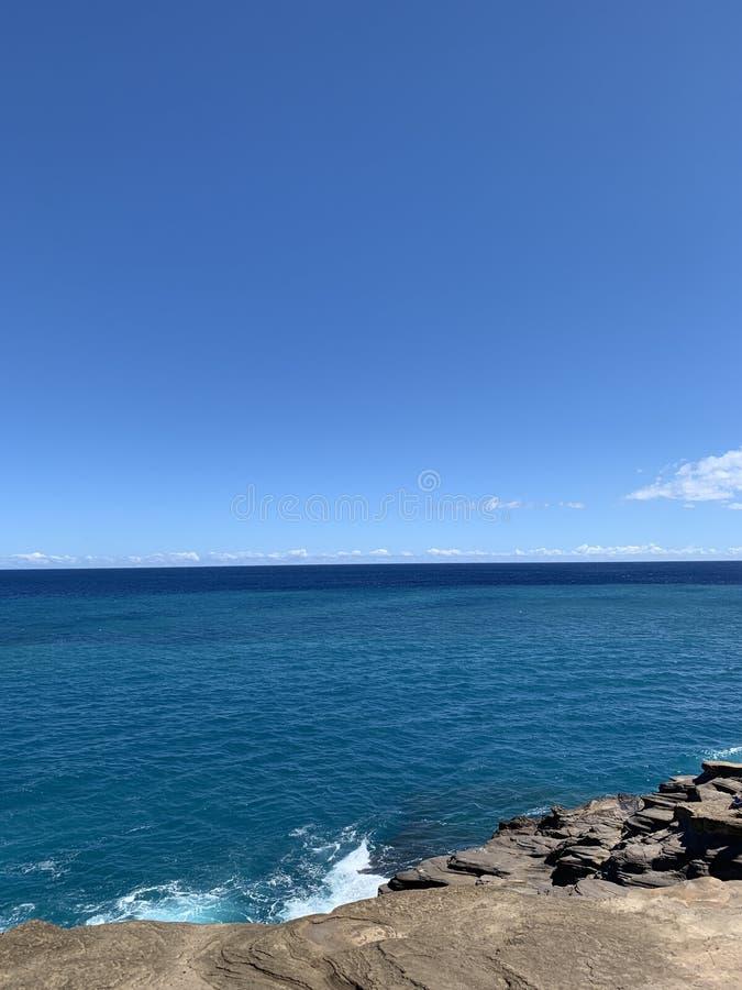 Vista del ritratto della caverna sputare delle Hawai di roccia e del cielo immagini stock