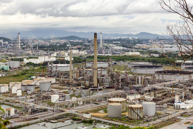 Vista del tanque con la refinería de petróleo y la planta industrial petroquímica con el cielo nublado y la montaña del fondo por fotos de archivo