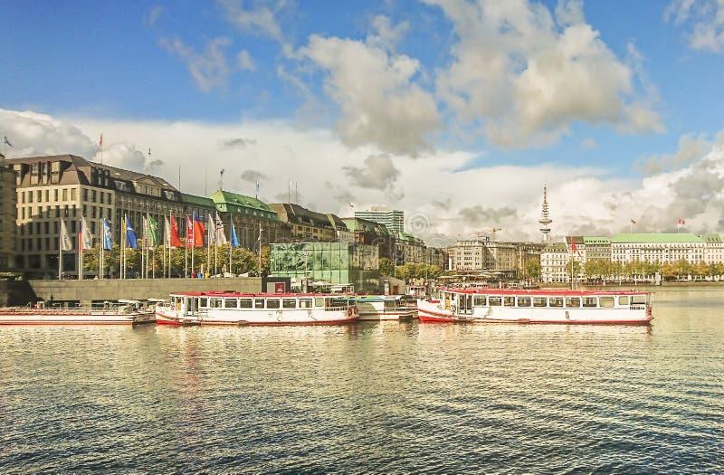 Vista del terraplén con las naves de la situación en el lado opuesto del río y de la parte de la ciudad de Hamburgo, Alemania fotografía de archivo libre de regalías