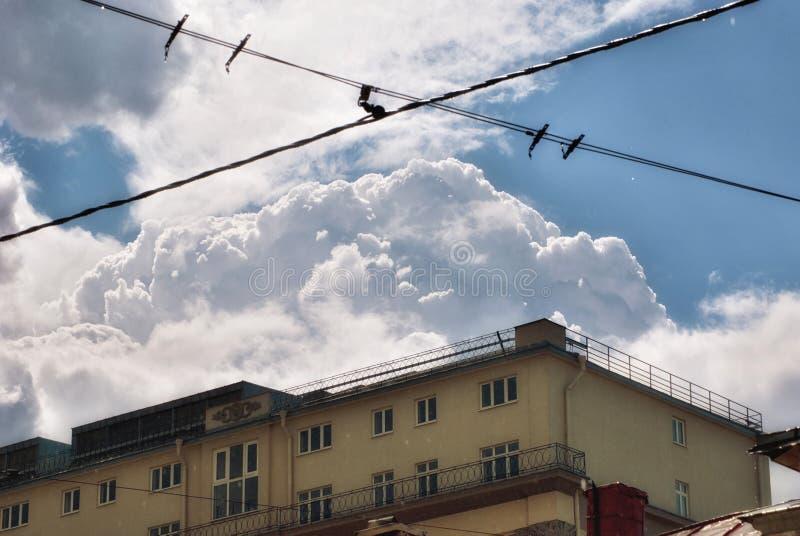 Vista del tetto di una casa della città nella pioggia in tempo soleggiato con le belle nuvole lanuginose fotografia stock