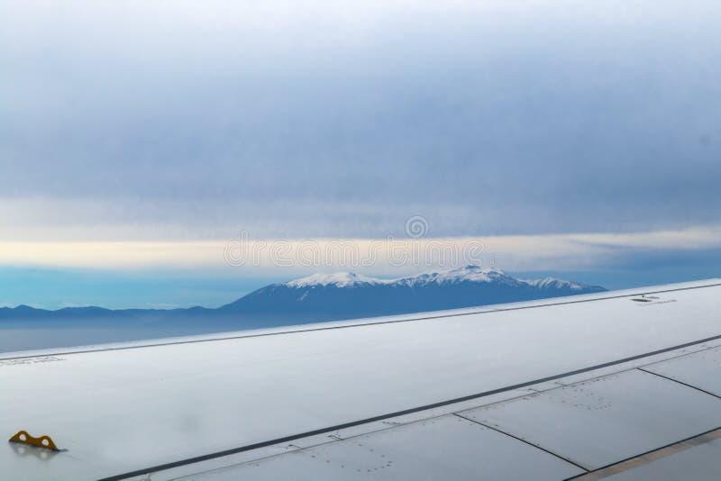 Vista del top de Mt Olympus en Grecia que empuja fuera de una niebla gruesa de un aeroplano con el ala en primero plano imágenes de archivo libres de regalías