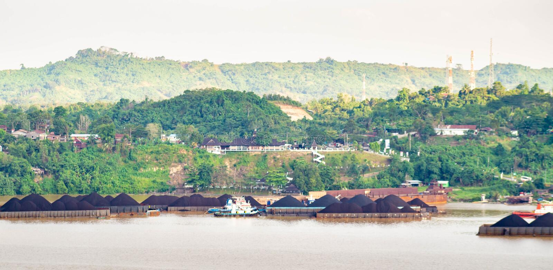 Vista del tráfico de los remolcadores que tiran de la gabarra del carbón en el río de Mahakam, Samarinda, Indonesia imagenes de archivo