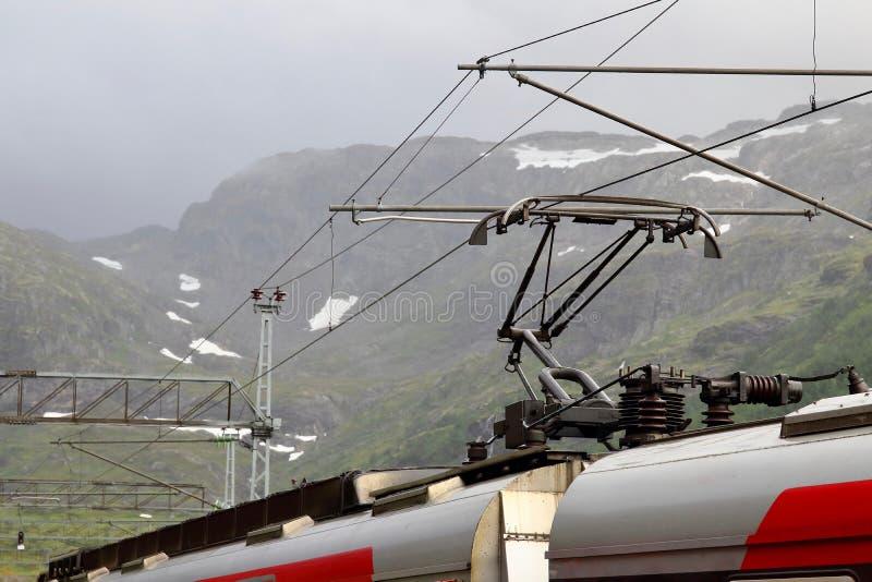 Vista del tren de la montaña de Voss parado en la estación de tren de Myrdal con los picos nevosos en el backgound, Noruega foto de archivo libre de regalías